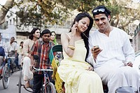 Young couple sitting in a rickshaw and listening to an MP3 player