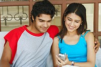 Close-up of a young couple sitting together holding a mobile phone