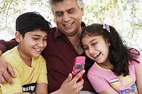 Close-up of a grandfather and his grandchildren looking at a mobile phone