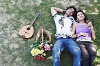 High angle view of a young couple lying together in the park