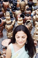 High angle view of a young woman standing with her eyes closed in a pottery store