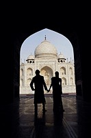 Silhouette of a couple standing in front of a mausoleum, Taj Mahal, Agra, Uttar Pradesh, India