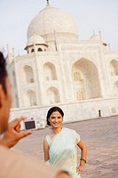 Rear view of a young man taking a photograph of a young woman in front of a mausoleum, Taj Mahal, Agra, Uttar Pradesh, India