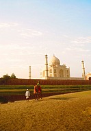 Mature man standing with a young man sitting on a camel, Taj Mahal, Agra, Uttar Pradesh, India