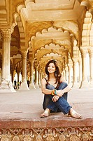 Young woman sitting on the floor smiling, Agra Fort, Agra, Uttar Pradesh, India