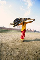 Rear view of a young woman holding her stole on the riverbank, Taj Mahal, Agra, Uttar Pradesh, India