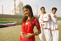 Portrait of a young woman smiling with two young men standing behind her on the riverbank, Taj Mahal, Agra, Uttar Pradesh, India
