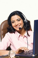 Portrait of a businesswoman wearing a headset and smiling in front of a laptop (thumbnail)