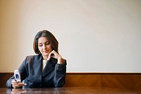Close-up of a businesswoman using a mobile phone in a conference room