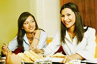 Close-up of two young women eating in a restaurant (thumbnail)