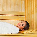 Portrait of a young woman lying in a sauna