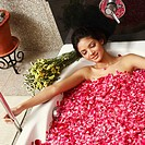High angle view of a young woman in a bathtub full of rose petals