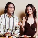 Portrait of a young couple sitting at the dining table and smiling