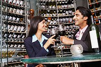 Businesswoman and a businessman toasting wine at a wine cellar