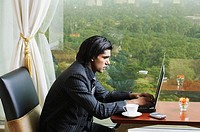 Side profile of a businessman sitting in an office and using a laptop