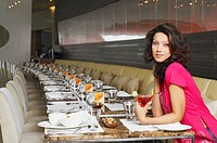 Portrait of a young woman sitting at a table in a restaurant