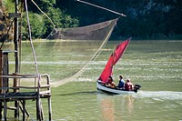 'Carrelet' fishing net and sailboat with red sail on Rance river. Brittany, France