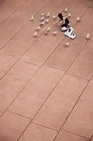 High angle view of woman feeding seagulls at city square