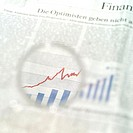 Close_up of magnifying glass on line graph