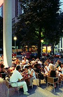 Tourists sitting at roadside cafe, Potsdamer Platz, Berlin, Germany