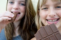 Portrait of two girls eating chocolates and smiling