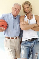 Portrait of a senior man and his son standing with a basketball