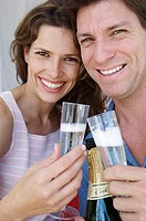 Portrait of a young couple smiling and holding champagne flutes