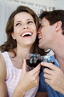 Close-up of a young couple smiling and toasting with wineglasses