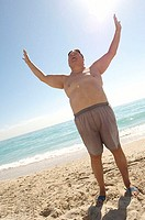 Low angle view of a mature man standing on the beach with his arms raised