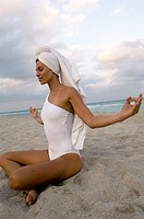 Side profile of a young woman meditating on the beach