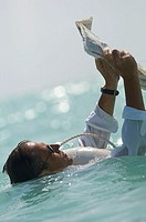 Side profile of a mature man floating in water and reading a newspaper
