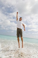 Low angle view of a mid adult man jumping on the beach with his hand raised