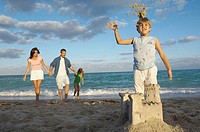 Boy standing behind a sandcastle with his parents and his sister walking behind him