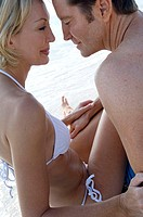 Side profile of a mid adult couple looking at each other on the beach