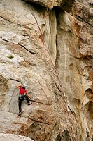 Female climber reaching the top of a route in the City of Rocks, Idaho, USA