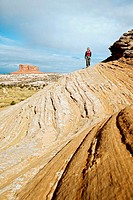 Female hiker on sandstone slickrock with Merrimac Butte in the background near Canyonlands National Park, Utah, USA