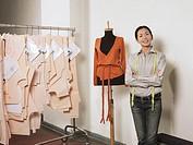 Fashion designer standing next to mannequin