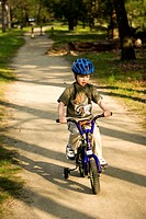 A 4-year-old boy riding a bike on a trail