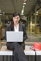 Woman using a laptop computer in factory