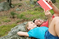 Father and daughter lying on rock and reading