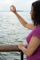 Woman circling statue of liberty with hand