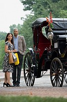 Couple stood next to horse drawn carriage