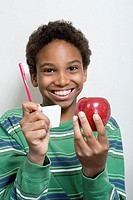 Boy holding apple and toothbrush