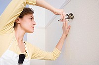 Woman pulling hooks out of wall