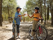 Boy and girl on bikes with water bottles
