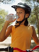 Girl on a bike drinking water