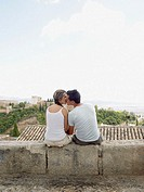 Couple on kissing on wall