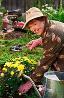 Senior woman planting flowers in garden.