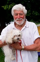 Senior man holding small white dog ( maltese)