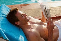 Man reading a book whilst on a sunlounger by a pool in India